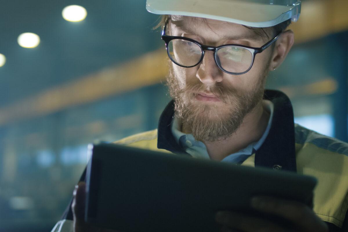 An engineer wearing a hardhat helmet using a tablet